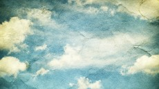 Vintage clouds and sky on crumpled paper texture.